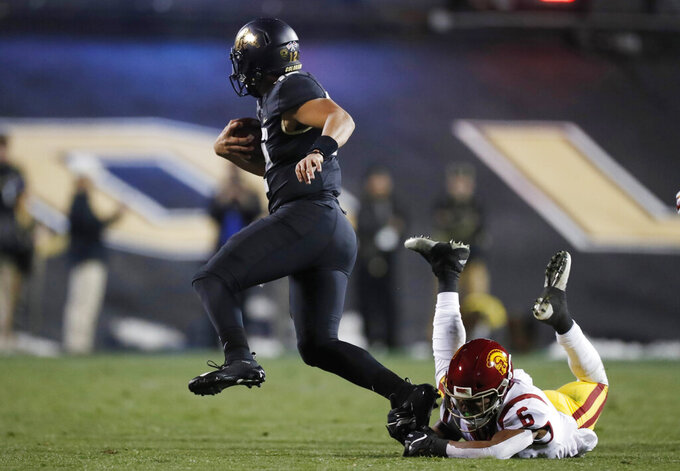 Colorado quarterback Steven Montez, left, slips past Southern California cornerback Isaac Taylor-Stuart for a short gain during the first half of an NCAA college football game Friday, Oct. 25, 2019, in Boulder, Colo. (AP Photo/David Zalubowski)