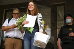 Russian journalist Svetlana Prokopyeva smiles holding a bunch of flowers after a court session in Pskov, Russia, Monday, July 6, 2020. A court in the city of Pskov convicted Prokopyeva on charges of condoning terrorism on Monday and ordered her to pay a fine in a case that has been widely criticized as an attack on freedom of speech. (AP Photo/George Markov)