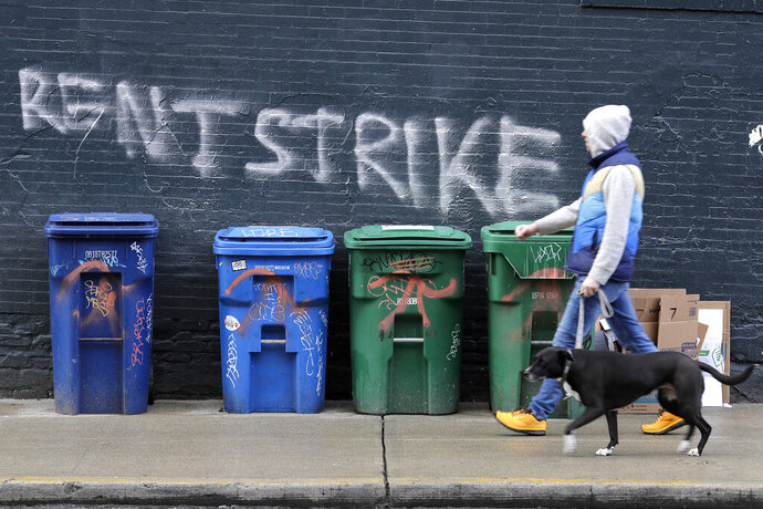 FILE - In this April 1, 2020, file photo, a pedestrian walks past graffiti that reads