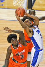 Pittsburgh forward Justin Champagnie (11) goes up for a shot as Miami center Nysier Brooks (3) defends during the second half an NCAA college basketball game in the first round of the Atlantic Coast Conference tournament in Greensboro, N.C., Tuesday, March 9, 2021. (AP Photo/Gerry Broome)