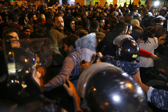 Riot police clash with protesters, as they try to remove them and open a road during an anti-government protest in Beirut, Lebanon, Wednesday, Dec. 4, 2019. Protesters have been holding demonstrations since Oct. 17 demanding an end to corruption and mismanagement by the political elite that has ruled the country for three decades. (AP Photo/Bilal Hussein)