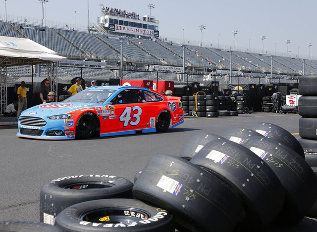 FILE - In this Sept. 4, 2015, file photo, Aric Almirola heads for the track during a NASCAR Sprint Cup auto racing practice session at Darlington Raceway in Darlington, S.C. When it resumes this Sunday, May 17, 2020, at Darlington, drivers will have their temperature taken as they enter the track and they will be wearing masks as they leave their isolated motorhomes and make their way to their cars. There will be no fans. (AP Photo/Terry Renna, File)