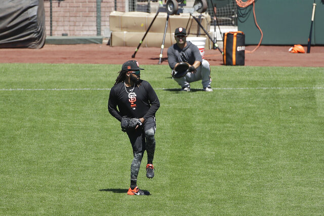 San Francisco Giants pitcher Johnny Cueto, foreground, throws to bullpen catcher Taira Uematsu during a baseball practice in San Francisco, Sunday, July 5, 2020. (AP Photo/Jeff Chiu)