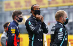 Mercedes driver Lewis Hamilton of Britain, center, stands on the podium after winning the Styrian Formula One Grand Prix race at the Red Bull Ring racetrack in Spielberg, Austria, Sunday, July 12, 2020. Third placed Red Bull driver Max Verstappen of the Netherlands on the left, second placed Mercedes driver Valtteri Bottas of Finland on the right. (Leonhard Foeger/Pool via AP)