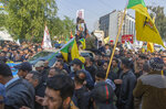 Mourners march during the funeral of Iran's top general Qassem Soleimani, 62, Abu Mahdi al-Muhandis, deputy commander of Iran-backed militias in Iraq known as the Popular Mobilization Forces and fellow militant leaders, in Baghdad, Iraq, Saturday, Jan. 4, 2020. Thousands of mourners chanting