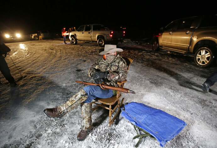FILE - In this Jan. 5, 2016 file photo Arizona rancher LaVoy Finicum holds a gun as he guards the Malheur National Wildlife Refuge near Burns, Ore. Finicum, one of the leaders of the armed takeover of the refuge, was later shot by state police officers after he fled an attempted police stop. Experts say right-wing extremism like the Malheur takeover had previously mostly played out in isolated pockets or smaller cities in America before the deadly assault by rioters on the U.S. Capitol earlier this month. (AP Photo/Rick Bowmer, File)