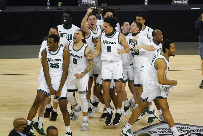 Cleveland State players celebrate following an NCAA college basketball game in the men's Horizon League conference tournament championship game against Oakland, Tuesday, March 9, 2021, in Indianapolis. Cleveland State won 80-69 (AP Photo/Darron Cummings)