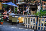 Customers dine outside PhoBar, Monday, June 22, 2020, in New York. New York City Mayor Bill de Blasio says he is delaying the planned resumption of indoor dining at restaurants in the city out of fear it would ignite a a spike in coronavirus infections. (AP Photo/John Minchillo)