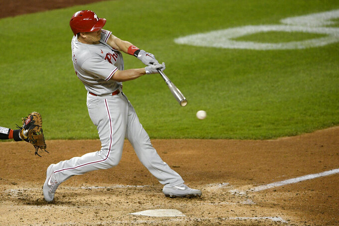 File-This Sept. 22, 2020, file photo shows Philadelphia Phillies' J.T. Realmuto batting during the second baseball game of a doubleheader against the Washington Nationals in Washington. Houston outfielder George Springer, New York Yankees second baseman DJ LeMahieu and Realmuto were among just six free agents who received $18.9 million qualifying offers on Sunday, Nov. 1, 2020, from their former teams. Three right-handed pitchers also received the offers, Cincinnati's Trevor Bauer, the New York Mets' Marcus Stroman, and San Francisco's Kevin Gausman. (AP Photo/Nick Wass, File)