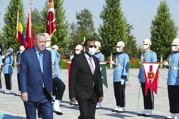 Turkish President Recep Tayyip Erdogan, left, and Ethiopian Prime Minister Abiy Ahmed review a military guard of honour in Ankara, Turkey, Wednesday, Aug. 18, 2021. Erdogan urged Wednesday a peaceful resolution of the Tigray conflict in Ethiopia and also said his country was willing to mediate between Addis Ababa and Sudan for a resolution of a border dispute.(Turkish Presidency via AP, Pool)