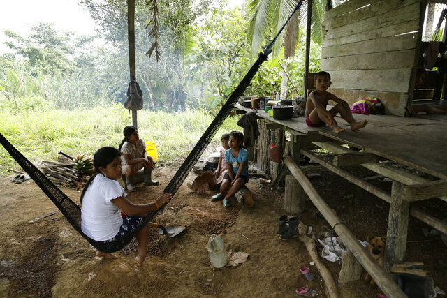 Members of the Ngabe Bugle indigenous group sit at their home in the jungle community of El Terron, Panama, Friday, Jan. 17, 2020. A pregnant woman, five of her children and a neighbor where round up by about 10 lay preachers at the hamlet on Monday and tortured, beaten, burned and hacked with machetes to make them