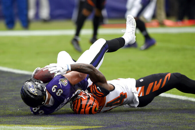 Baltimore Ravens tight end Mark Andrews (89) holds on to the ball after making a touchdown catch on a pass from quarterback Lamar Jackson, not visible, against Cincinnati Bengals strong safety Vonn Bell, right, during the first half of an NFL football game, Sunday, Oct. 11, 2020, in Baltimore. (AP Photo/Gail Burton)