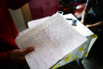 In this May 29, 2019 photo, inmate Federico Gonzalez, also known as Kung-Fu OmBijam, holds his handwritten lyrics inside his cell at the Punta de Rieles prison in Montevideo, Uruguay. Federico is a well known rap singer who is usually allowed to perform outside the prison. (AP Photo/Matilde Campodonico)