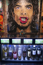 Art by Josh Wingerter lines the walls around Stained Glass Wine House, a wine bar in downtown Gretna, La. (Ian McNulty/The Times-Picayune/The New Orleans Advocate via AP)