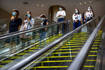 People wearing face masks to protect against the coronavirus ride escalators at a shopping mall in Beijing, Friday, Aug. 14, 2020. China's factory output rose just under 5% last month from a year earlier while retail sales fell slightly, suggesting the country's recovery from the coronavirus pandemic remains muted. (AP Photo/Mark Schiefelbein)