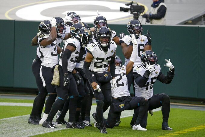 The Jacksonville Jaguars defense celebrates after Sidney Jones intercepted a pass during the second half of an NFL football game against the Green Bay Packers Sunday, Nov. 15, 2020, in Green Bay, Wis. (AP Photo/Mike Roemer)