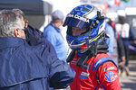 Ryan Briscoe, right, talks with a crew member outside his pit stall during a practice session for the Rolex 24 hour race at Daytona International Speedway, Friday, Jan. 29, 2021, in Daytona Beach, Fla. (AP Photo/John Raoux)