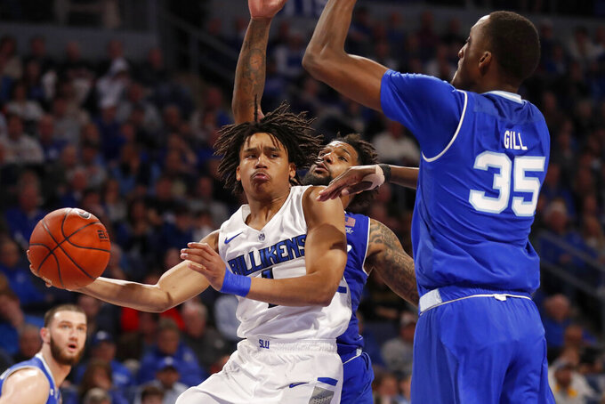 Saint Louis' Yuri Collins, front left, passes around Seton Hall's Romaro Gill (35) during the second half of an NCAA college basketball game Sunday, Nov. 17, 2019, in St. Louis. (AP Photo/Jeff Roberson)