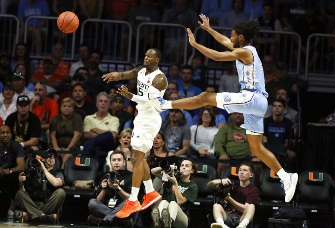 Miami center Ebuka Izundu passes the ball against North Carolina guard Coby White during the first half of an NCAA college basketball game on Saturday, Jan. 19, 2019, in Coral Gables, Fla. (AP Photo/Brynn Anderson)