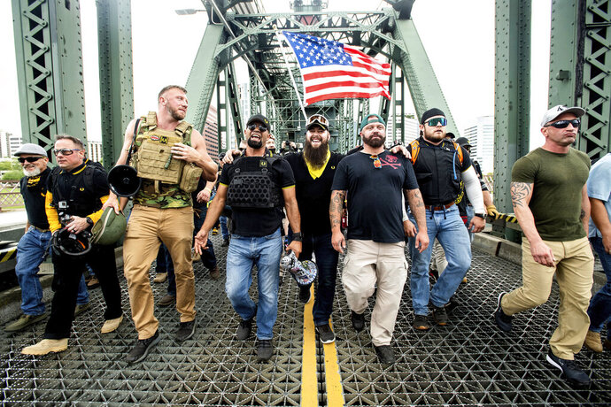 FILE - Members of the Proud Boys, including organizer Joe Biggs, third from right, march across the Hawthorne Bridge during an