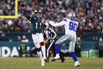 Philadelphia Eagles quarterback Carson Wentz (11) throws a pass as Dallas Cowboys defensive end Demarcus Lawrence defends during the first half of an NFL football game Sunday, Dec. 22, 2019, in Philadelphia. (AP Photo/Michael Perez)