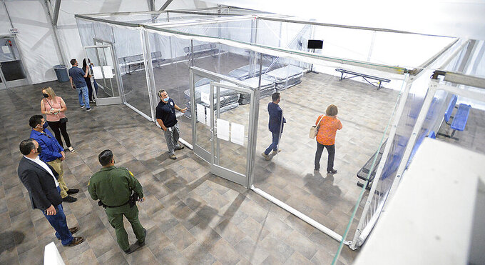 People touring the U.S. Border Patrol Yuma Sector, soft-sided processing facility, look at the pods inside one of four living areas at the facility during an open house, Tuesday, April 20, 2021, in Yuma, Ariz., in which the public was invited to see how the USBP will handle detained illegal immigrants who are apprehended while crossing the border into the United States from Mexico. The facility includes a laundry facility; multipurpose shower and changing area; an intake and medical area; processing area; 15 private phone rooms; and the four living areas, each divided into eight pods. (Randy Hoeft/The Yuma Sun via AP)