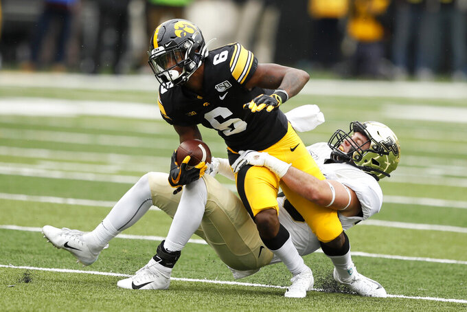 Iowa wide receiver Ihmir Smith-Marsette (6) is tackled by Purdue safety Brennan Thieneman, right, after catching a pass during the second half of an NCAA college football game, Saturday, Oct. 19, 2019, in Iowa City, Iowa. Iowa won 26-20. (AP Photo/Charlie Neibergall)