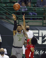 Baylor guard MaCio Teague (31) shoots a three-point basket over Texas Tech guard Kyler Edwards in the second half of an NCAA college basketball game Sunday, March 7, 2021, in Waco, Texas. (AP Photo/Jerry Larson)