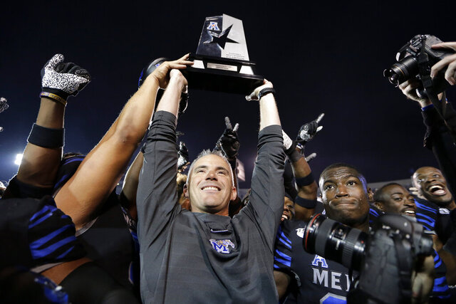 Memphis head coach Mike Norvell lifts the American Athletic Conference West Division championship trophy after his team defeated Cincinnati in an NCAA college football game Friday, Nov. 29, 2019, in Memphis, Tenn. Memphis is to play Cincinnati again next week in Memphis in the conference championship game. (AP Photo/Mark Humphrey)