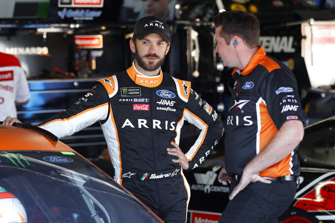 Daniel Suarez, left, talks with a crew member during practice for a NASCAR Cup Series auto race at Michigan International Speedway in Brooklyn, Mich., Saturday, Aug. 10, 2019. (AP Photo/Paul Sancya)