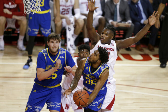 UC Riverside's Callum McRae, left, watches as George Willborn III (35) goes to the basket against Nebraska's Cam Mack, rear center, and Yvan Ouedraogo, right, during the first half of an NCAA college basketball game in Lincoln, Neb., Tuesday, Nov. 5, 2019. (AP Photo/Nati Harnik)