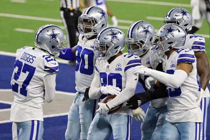 Dallas Cowboys' Trevon Diggs (27), DeMarcus Lawrence (90) and others celebrate with Anthony Brown (30), after Brown intercepted a Philadelphia Eagles quarterback Jalen Hurts pass in the end zone late in the second half of an NFL football game in Arlington, Texas, Sunday, Dec. 27. 2020. (AP Photo/Michael Ainsworth)