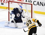 Pittsburgh Penguins' Jake Guentzel (59) scores on Winnipeg Jets goaltender Laurent Brossoit (30) during the third period of an NHL hockey game, Sunday, Oct. 13, 2019, in Winnipeg, Manitoba. (Fred Greenslade/The Canadian Press via AP)