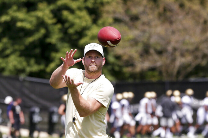 In this Friday, Aug. 2, 2019, photo, Purdue offensive coordinator Brian Brohm catches a ball during practice in West Lafayette, Ind. Brian Brohm went through his usual practice routine this week. He met with his older brother, Jeff, about game planning and the initial play-calling script as he prepared for Saturday's long-awaited season opener against Iowa. Less than a week after the Boilermakers fourth-year head coach tested positive for COVID-19 and was forced into isolation for 10 days, it's the other Brohm taking charge this weekend.(Nikos Frazier/Journal & Courier via AP)