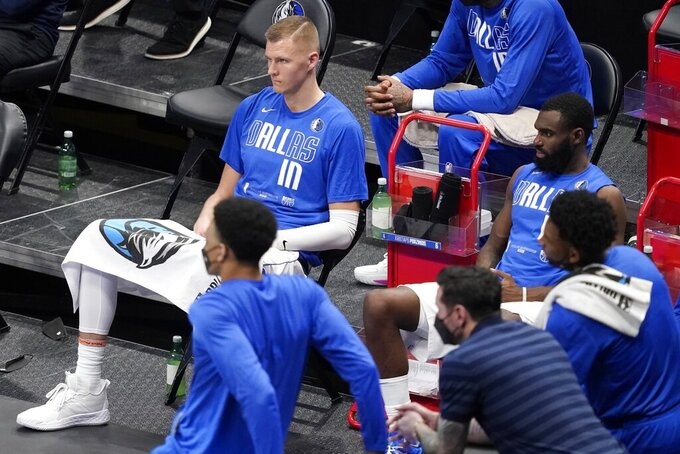 Dallas Mavericks' Kristaps Porzingis, top left, and Tim Hardaway Jr., right, sit on the bench watching the final minutes of Game 4 of an NBA basketball first-round playoff series against the Los Angeles Clippers in Dallas, Sunday, May 30, 2021. The Clippers won 106-81. (AP Photo/Tony Gutierrez)