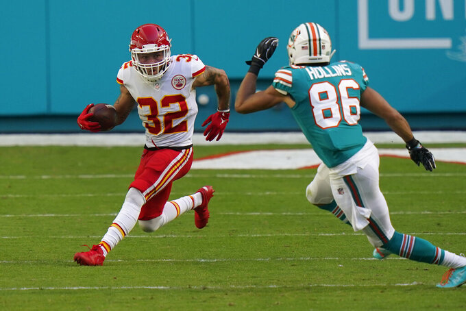 Kansas City Chiefs wide receiver Gehrig Dieter (12) runs after intercepting a pass as Miami Dolphins wide receiver Mack Hollins (86) attempts to defend, during the first half of an NFL football game, Sunday, Dec. 13, 2020, in Miami Gardens, Fla. (AP Photo/Lynne Sladky)