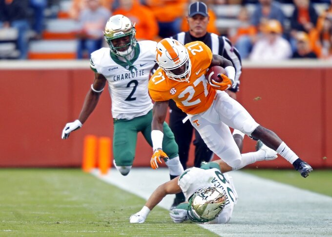 Tennessee's Carlin Fils-aime (27) is knocked out of bounds by Charlotte defensive back Ben DeLuca (28) in the first half of an NCAA college football game Saturday, Nov. 3, 2018, in Knoxville, Tenn. (AP Photo/Wade Payne)