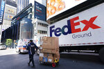 A FedEx driver delivers a cart of packages, Thursday, May 6, 2021, in New York. FedEx is getting hurt by the tight job market. The package delivery company said Tuesday, Sept. 21 that its costs are up $450 million in the most recent quarter, as it paid higher wages as it got harder to find new workers and demand for shipping increased. (AP Photo/Mark Lennihan)