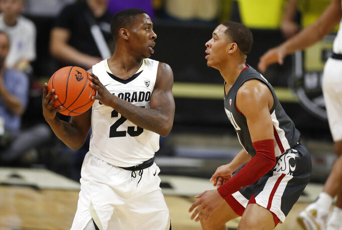 Colorado guard McKinley Wright IV, left, looks to pass the ball as Washington State guard Jervae Robinson defends in the first half of an NCAA college basketball game Thursday, Jan. 23, 2020, in Boulder, Colo. (AP Photo/David Zalubowski)