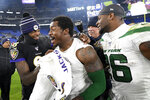 Baltimore Ravens quarterback Lamar Jackson, left, laughs with New York Jets outside linebacker James Burgess, center, as running back Le'Veon Bell, right, looks on after an NFL football game, Thursday, Dec. 12, 2019, in Baltimore. The Ravens won 42-21. (AP Photo/Nick Wass)