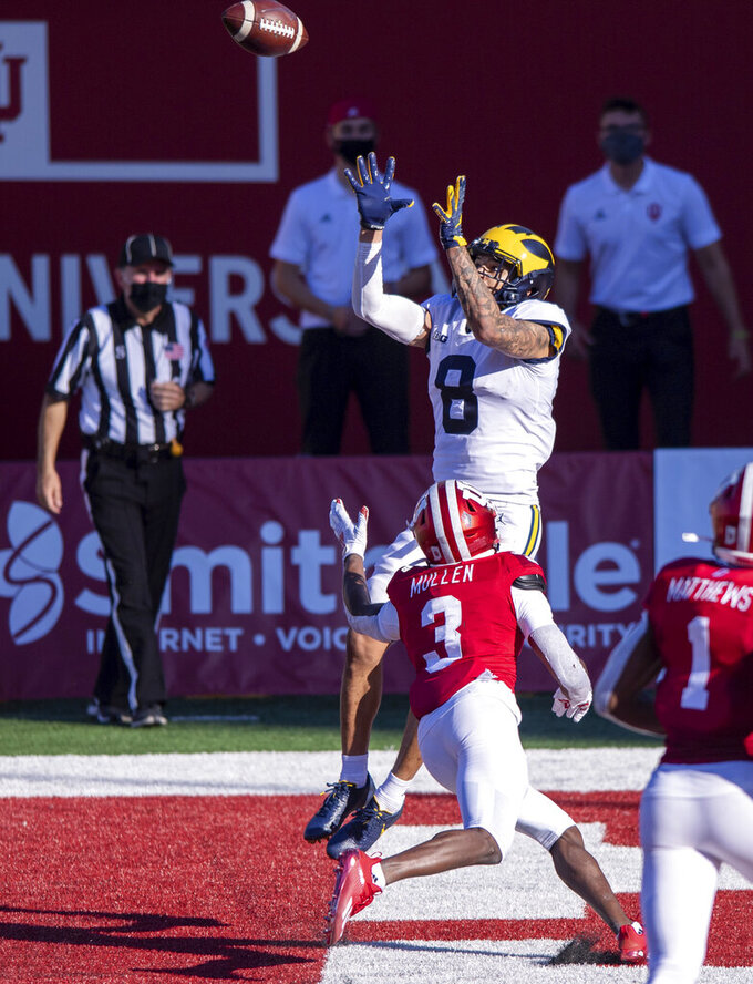 Michigan wide receiver Ronnie Bell (8) goes up for the catch in the end zone to score as he's defended by Indiana defensive back Tiawan Mullen (3) during the second half of an NCAA college football game Saturday, Nov. 7, 2020, in Bloomington, Ind. Indiana won 38-21. (AP Photo/Doug McSchooler)