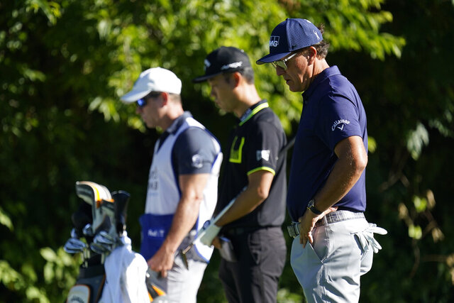 Phil Mickelson, right, Kevin Na, center, and their caddie observe a moment of silence on the 13th tee during the first round of the Charles Schwab Challenge golf tournament at the Colonial Country Club in Fort Worth, Texas, Thursday, June 11, 2020. Players at the 8:46 a.m. tee time paused to pay their respects to the memory of George Floyd for a moment of silence, prayer and reflection. (AP Photo/David J. Phillip)
