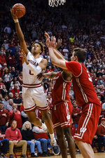 Indiana guard Romeo Langford, left, shoots and scores next to Wisconsin defenders guard Khalil Iverson, center, and Nate Reuvers during the second overtime of an NCAA college basketball game in Bloomington, Ind., Tuesday, Feb. 26, 2019. Indiana won 75-73. (AP Photo/AJ Mast)