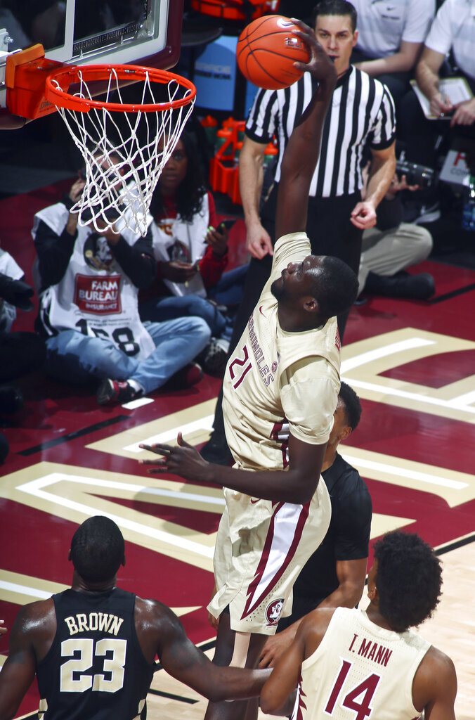 Florida State center Christ Koumadje (21) dunks as Wake Forest guard Chaundee Brown (23) and Florida State guard Terance Mann (14) watch during the first half of an NCAA college basketball game in Tallahassee, Fla., Wednesday, Feb. 13, 2019. (AP Photo/Phil Sears)
