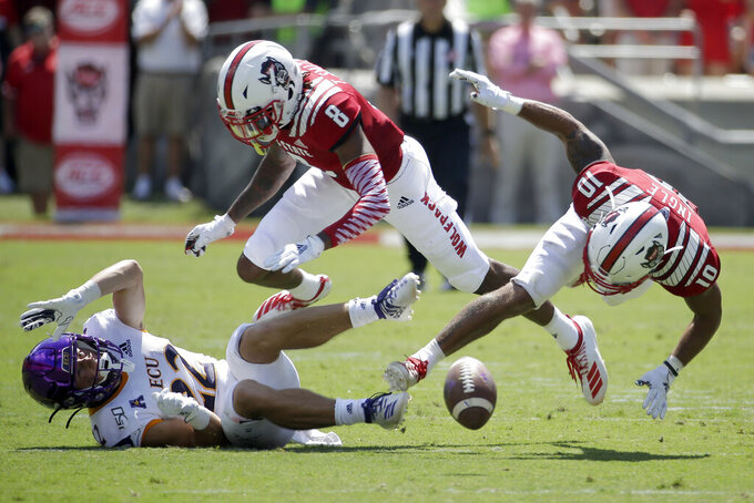 North Carolina State cornerback Teshaun Smith (8) and safety Tanner Ingle (10) struggle with East Carolina wide receiver Tyler Snead (22) for a pass during the first half of an NCAA college football game in Raleigh, N.C., Saturday, Aug. 31, 2019. (AP Photo/Gerry Broome)