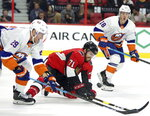 New York Islanders center Brock Nelson (29) and Ottawa Senators center Chris Tierney (71) battle for the puck as New York Islanders left wing Anthony Beauvillier (18) looks on during first-period NHL hockey game action in Ottawa, Ontario, Friday, Oct. 25, 2019. (Fred Chartrand/The Canadian Press via AP)