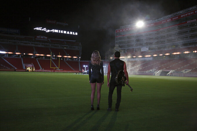 This July 25, 2019, photo provided by Jon-Paul Bruno shows Shannon Haley and Ryan Michaels during the shooting of a music video at Levi's Stadium in Santa Clara, Calif. NFL players' dreams usually center on scoring touchdowns and making game-saving tackles. Then they watch videos of their performances. It's not that much different for musicians, particularly the husband/wife country duo of Shannon Haley and Ryan Michaels. Their big play occurred in Levi's Stadium, home of their longtime favorite team, the 49ers. (Jon-Paul Bruno via AP)