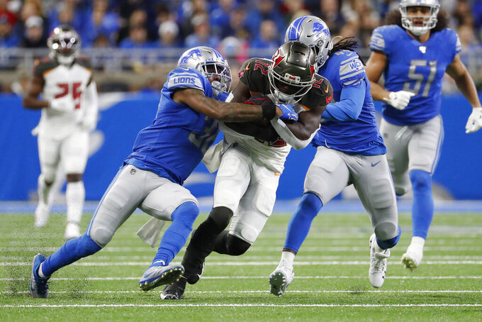 Tampa Bay Buccaneers wide receiver Chris Godwin is tackled by Detroit Lions strong safety Tavon Wilson, left, and linebacker Jalen Reeves-Maybin, right, during the first half of an NFL football game, Sunday, Dec. 15, 2019, in Detroit. (AP Photo/Rick Osentoski)