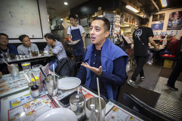 In this Dec. 13, 2019, photo, Martin Khan of Capital Cafe talks about the effects on his business after he says his store was incorrectly labeled as an anti-protest
