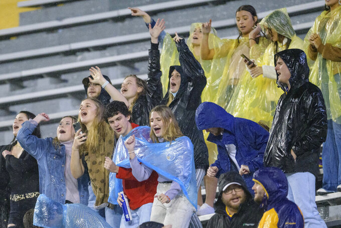 LSU fans cheer in the rain during the first half of an NCAA college football game against Mississippi in Baton Rouge, La., Saturday, Dec. 19, 2020. (AP Photo/Matthew Hinton)
